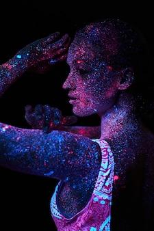 Mulher sob luz ultravioleta com o corpo todo coberto por gotículas coloridas