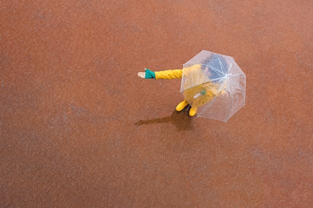 Mulher sob um guarda-chuva transparente, estendendo a mão para testar se chove. copie o espaço. terra traseira vermelha