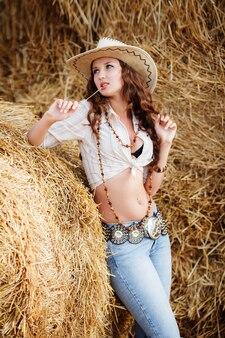 Mulher sobre fundo de feno. jovem mulher com roupas de estilo cowboy