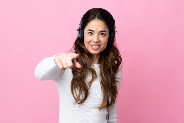 Mulher sobre música rosa isolada e apontando para a frente