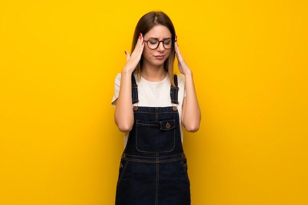 Mulher, sobre, parede amarela, com, dor de cabeça