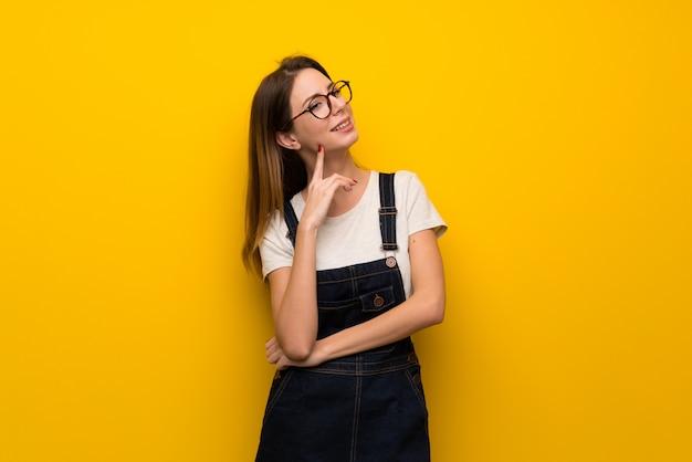 Mulher, sobre, parede amarela, pensando, um, idéia, enquanto, olhar