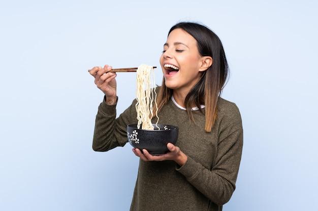 Mulher sobre parede azul isolada, segurando uma tigela de macarrão com pauzinhos e comê-lo