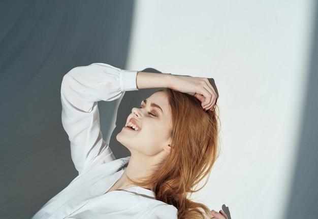 Mulher sobre um fundo claro no modelo de cabelo vermelho de maquiagem de roupas brancas. foto de alta qualidade