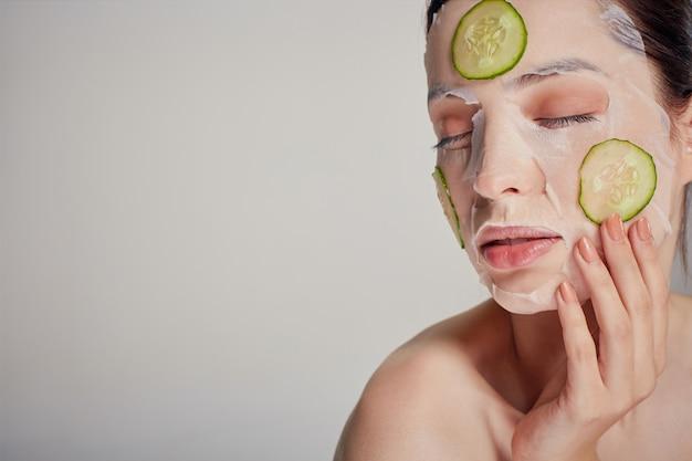 Mulher sofisticada em uma máscara hidratante com um pepino fresco no rosto a sério com os olhos fechados e a mão perto do rosto