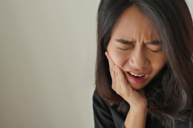 Mulher sofrendo de dor de dente, menina com cárie dentária, sensibilidade, conceito de tratamento odontológico