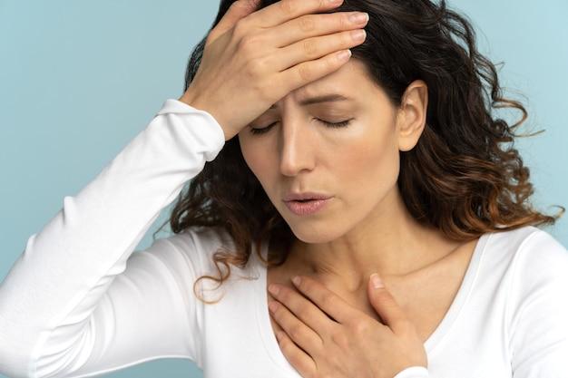 Mulher sofreu uma insolação em um clima quente de verão, tocando sua testa. dor no peito, vertigem, enxaqueca
