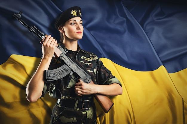 Mulher soldado de uniforme na bandeira ucraniana