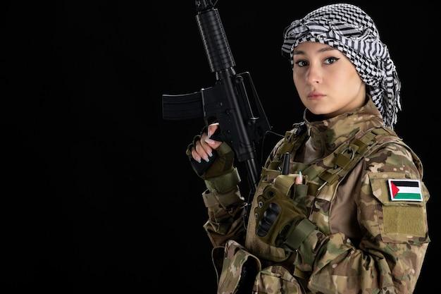 Mulher soldado em uniforme militar com parede preta de metralhadora