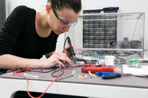 Mulher, soldering, pedaços, tabela