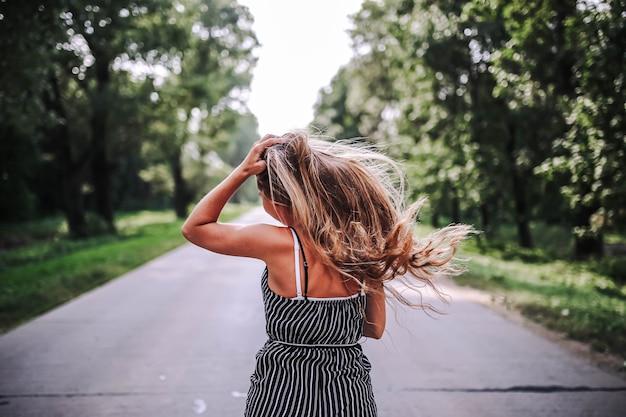 Mulher solitária caminha ao longo da estrada entre a floresta para encontrar uma nova vida no verão