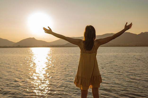 Mulher solitária e pensativa com os braços abertos em adoração ao sol refletindo na água do mar ao pôr do sol ou nascer do sol