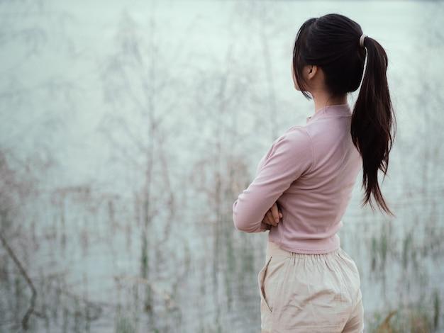 Mulher solitária em pé sozinho ao lado do rio. solitário, conceito de tristeza.