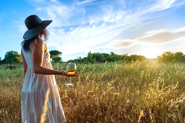 Mulher solitária irreconhecível em um vestido branco boho com grande chapéu escuro, segurando uma taça de vinho na mão