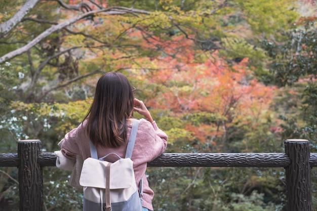 Mulher solitária permanente ausente minded e olhando para as folhas mudam de cor no outono
