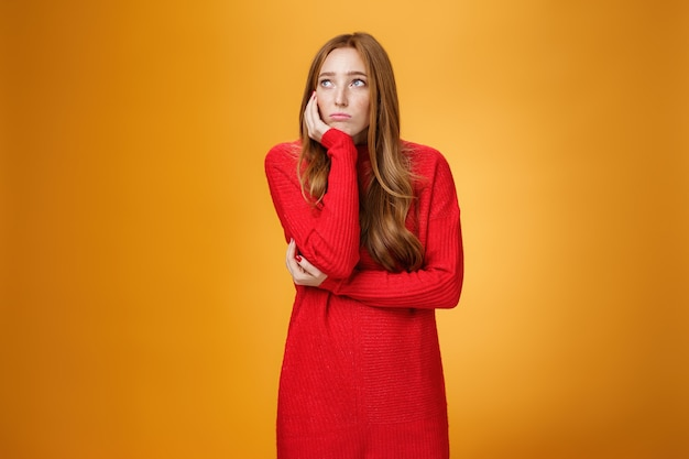 Mulher solitária triste e chateada, inclinando a cabeça na palma da mão em pose chateada, parecendo sombria no canto superior esquerdo, lembrando de uma história infeliz ou ficando entediada em pé inquieto sobre uma parede laranja