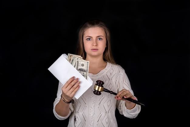 Mulher solta segurando um martelo e um envelope com dinheiro