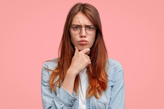Mulher sombria e descontente com rosto sardento, segura o queixo e franze a testa, está de mau humor, faz careta de descontentamento, usa jaqueta jeans, isolada em fundo rosa