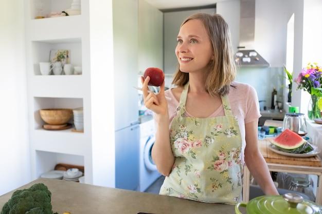 Mulher sonhadora alegre segurando frutas, olhando para longe e sorrindo enquanto cozinha em sua cozinha. copie o espaço. cozinhando em casa e conceito de alimentação saudável
