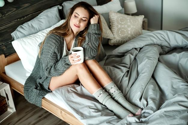 Mulher sonhadora com café olhando pela janela