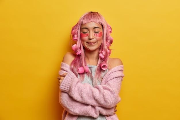 Mulher sonhadora de aparência agradável com cabelo rosa, se abraça suavemente, gosta da maciez do macacão quente, usa bobes, faz penteado perfeito