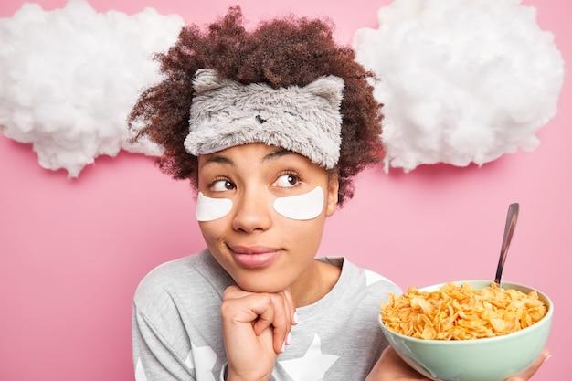 Mulher sonhadora de cabelos cacheados segura a mão sob o queixo e olha pensativamente para o lado, perdida em pensamentos enquanto toma o café da manhã e come flocos de milho, usa máscara de dormir e pijama isolado na parede rosa