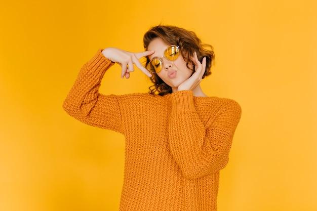 Mulher sonhadora em suéter da moda posando com expressão facial de beijo e olhos fechados