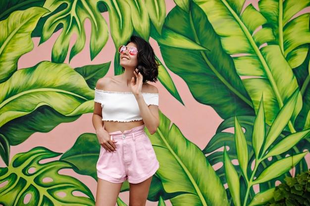 Mulher sonhadora em traje de verão olhando para cima com um sorriso