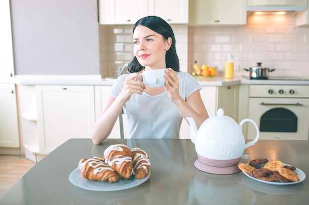 Mulher sonhadora senta-se à mesa e olha para a direita. ela segura um copo branco nas mãos. há chaleira e pratos com biscoitos e croissans à mesa.
