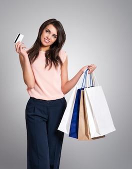 Mulher sonhando com cartão de crédito e sacolas de compras