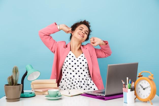 Mulher sonolenta esticando o corpo com os olhos fechados enquanto trabalha em uma mesa isolada sobre a parede azul