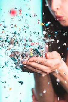 Mulher soprando confete das mãos dela
