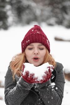 Mulher soprando em uma pilha de neve