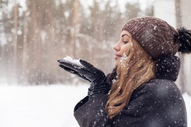 Mulher soprando neve em um parque