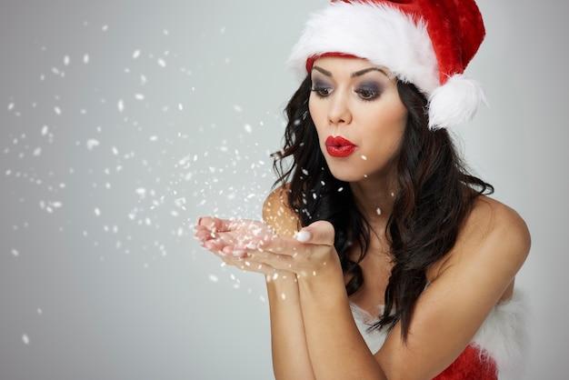 Mulher soprando pequenos pedaços de neve