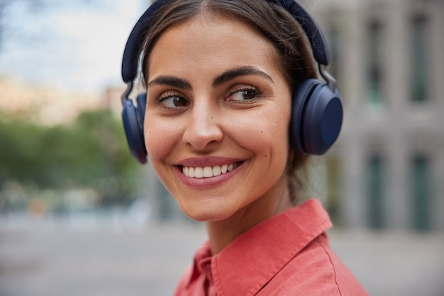 Mulher sorri agradavelmente mostra dentes brancos olhando para o lado usa poses de camisa vermelha contra desfocado