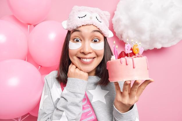 Mulher sorri alegremente comemora aniversário em ambiente doméstico usa máscara de dormir e pijama com bolo delicioso
