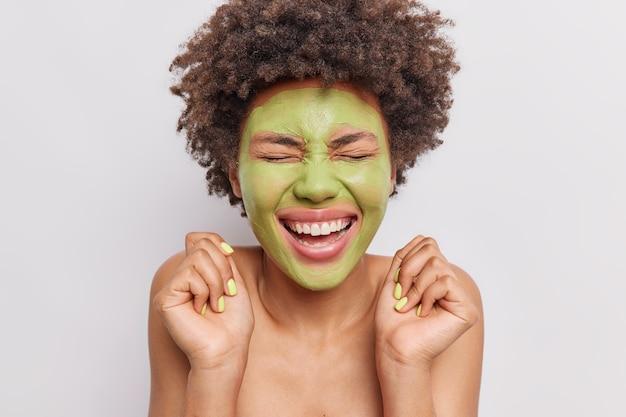 Mulher sorri amplamente aplica máscara de cuidados com a pele, levanta as mãos obtém tratamentos de beleza isolados no branco