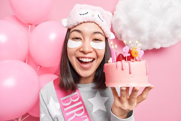 Mulher sorri amplamente aplica patches de beleza para reduzir as rugas segura um bolo delicioso com velas acesas vestida de pijama tem clima festivo comemora aniversário