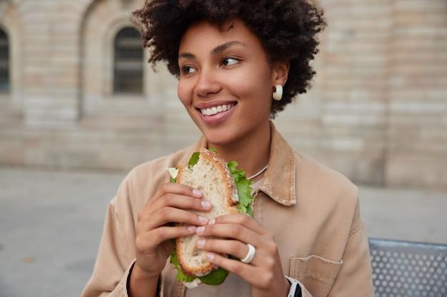 Mulher sorri amplamente, come sanduíche saboroso e sente fome depois de passear pela cidade vestida com roupas casuais desviando o olhar alegremente poses ao ar livre