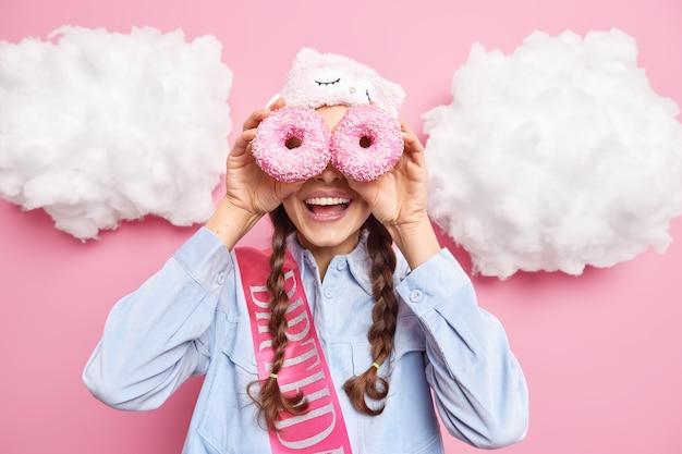 Mulher sorri com alegria contra os olhos com rosquinhas doces vidradas gosta de comer uma padaria deliciosa usa camisa de máscara de dormir e fita de aniversário isolada em rosa