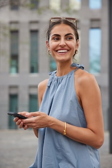Mulher sorri com os dentes segurando o celular nas mãos cria publicação de viagens e compartilha nas redes sociais trabalho feliz em ler mensagem recebida. ela usa óculos de sol com camiseta azul