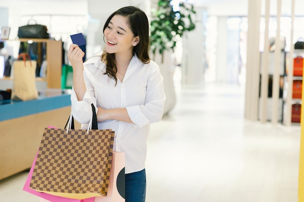 Mulher sorri com sacos de compras desfrutar de usar cartão de crédito em shopping center