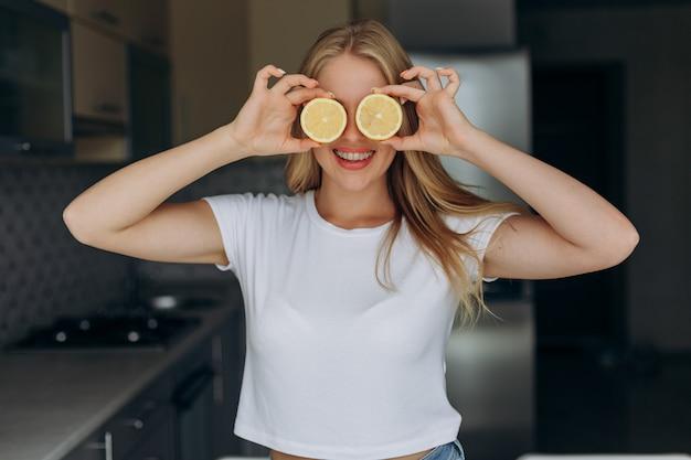 Mulher sorri, com, um, salada fruta tropical, sendo, brincalhão, cobertura, dela, olhos, com, limão