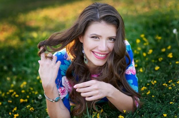 Mulher sorri em uma clareira verde verão com flores.
