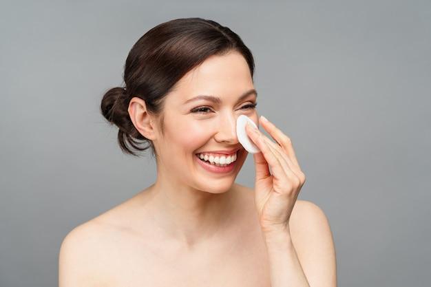 Mulher sorri uma mulher natural com boa pele limpa o rosto com um algodão cosmetologia de spa