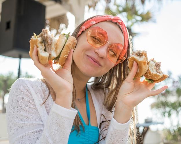 Mulher sorridente a comer hambúrgueres na praia