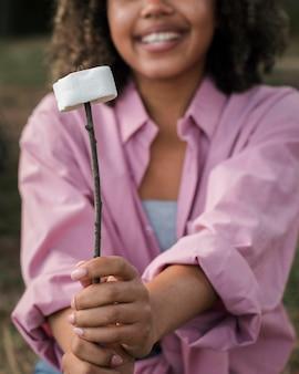 Mulher sorridente a comer marshmallow enquanto acampa