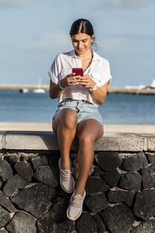 Mulher sorridente a enviar mensagens ao telemóvel à beira-mar