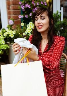 Mulher sorridente a olhar para uma promoção a comprar roupas